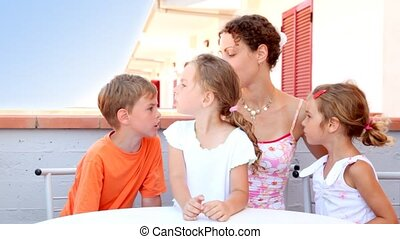 Woman and three kids are sitting at balcony and boy is...