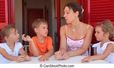 Woman and three kids are sitting at the table and talking