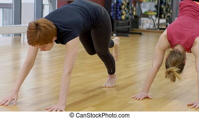 Woman and yoga instructor do pose during training in...