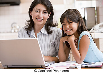 Woman and young girl in kitchen with laptop and paperwork...