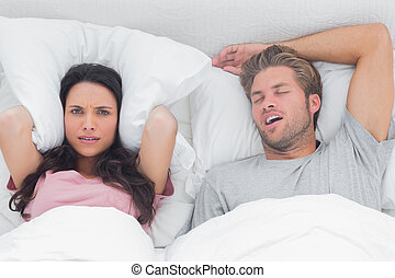 Woman annoyed by the snoring of her - Woman covering ears...