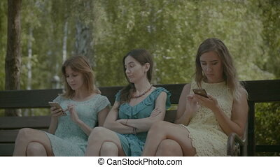 Woman annoyed by two friends busy with their phones
