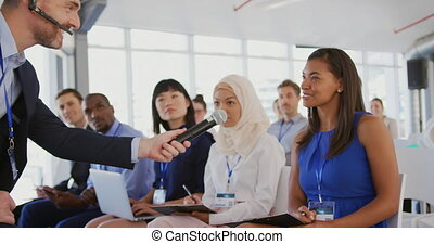 Woman answering at a question during a seminar - A Caucasian...