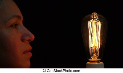 Woman Antique Filament Bulb Amused - Close up side view shot...