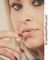 Woman applies lip balm cream to her lips