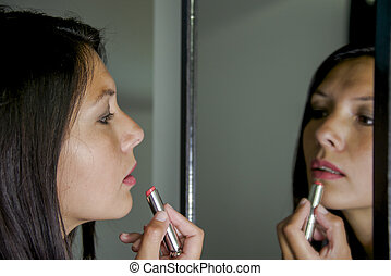 woman applies lipstick in front of mirror
