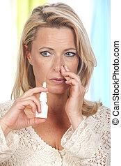 Woman applies nasal spray