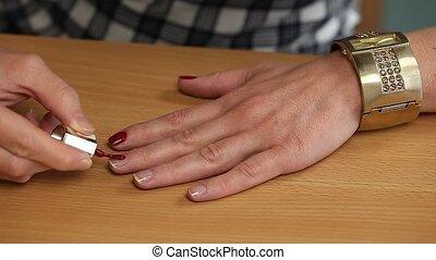 Woman apply red nail polish