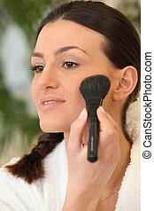 Woman applying blush on the cheek