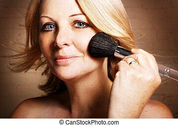 Woman applying blusher