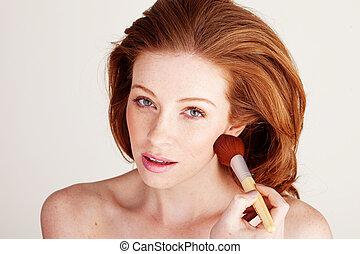 Woman Applying Blusher To Her Cheek