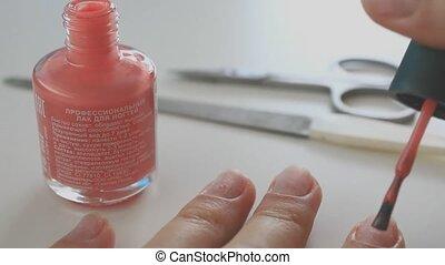 Woman applying coral nail polish - Woman applying coral...