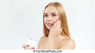 Woman Applying Cream on Face - Pretty lady with blond hair...