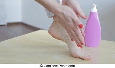Woman applying cream on foot