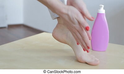 Woman applying cream on foot