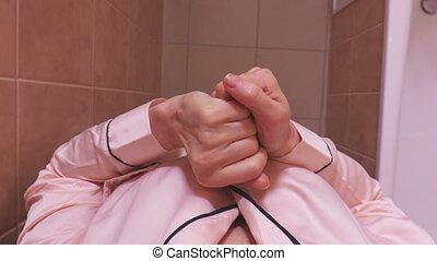 Woman applying cream on hands at bathroom