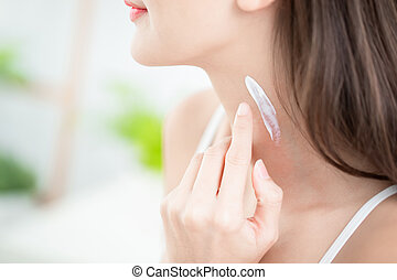 woman applying cream on neck