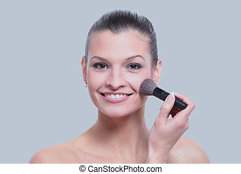 Woman applying dry cosmetic tonal foundation on the face...