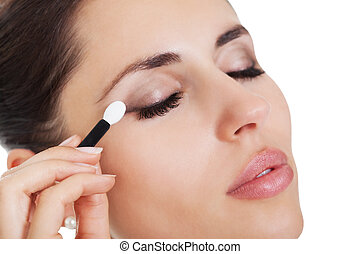 Beautiful young brunette woman applying eye shadow from a small portable compact set of colours isolated on white