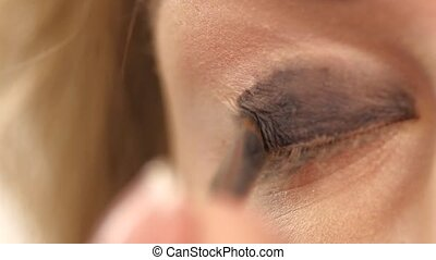 woman applying eyeshadow powder, Close up. Slow motion