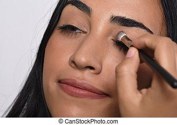 Young beautiful woman applying eyeshadow. Isolated white background.
