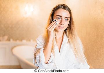 Woman applying facial cosmetic cream, skincare