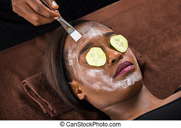 Woman Applying Facial Mask In Spa