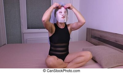 Woman applying facial mask