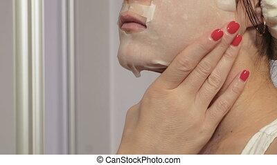 Woman applying facial sheet mask. Beauty Skin Care Concept