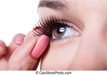 Woman applying false eyelashes - Close-up of a woman ...