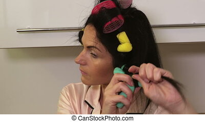 Woman applying hair rollers on her hairs