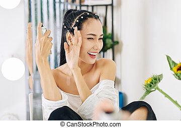 Woman applying hair spray - Young Asian woman squinting eyes...