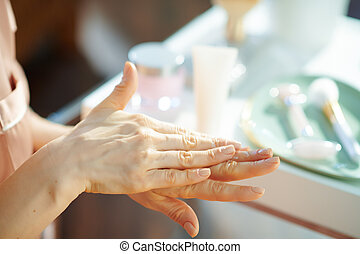 woman applying hand cream at home in sunny winter day