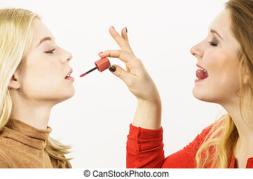 Woman applying her friend lipstick on lips
