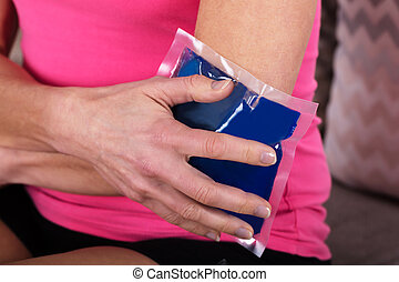Woman Applying Ice Bag On Her Elbow