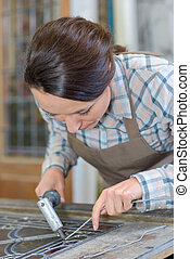 Woman applying lead to stained glass
