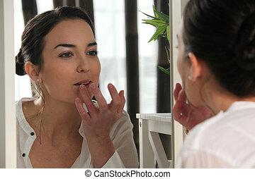 Woman applying lip gloss in a mirror