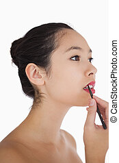 Woman applying lip liner on white background