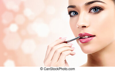woman applying lips makeup with cosmetic brush