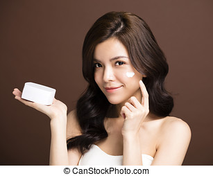 woman applying lotion cream on face
