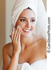 Woman applying lotion - A shot of a young beautiful woman...