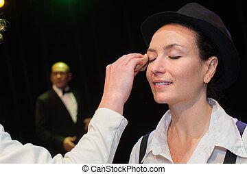 woman applying make-up by make-up artist