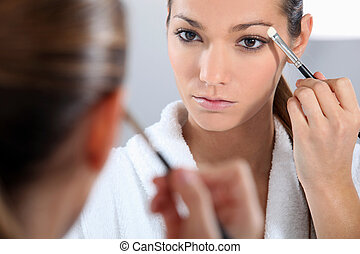 Woman applying make-up in bathroom