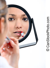 Woman applying make-up in mirror