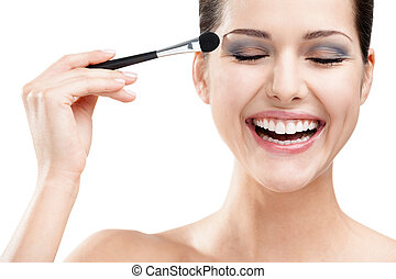 Woman applying make-up with brush, isolated on white. Beauty procedures