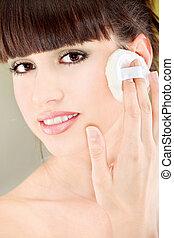 woman applying make up with cosmetic sponge