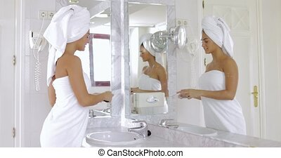 Woman applying makeup in bathroom - Young fit girl wrapped...