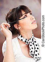 woman applying makeup on eyelash