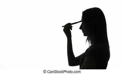 Woman applying makeup - Silhouette of a woman applying...