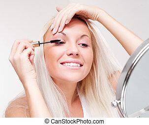 woman applying mascara - beautiful happy young woman doing...